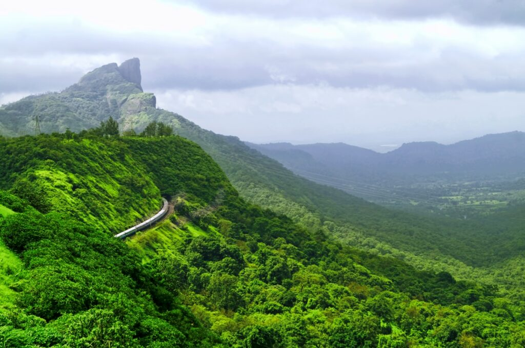 A train passing through the tunnel that has been carved through the beautiful landscape of the mountains on the Mumbai Pune railway track
